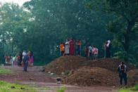 People gather to watch the wreckage of an Air India Express jet at Calicut International Airport in Karipur, Kerala, on August 8, 2020. - Fierce rain and winds lashed a plane carrying 190 people before it crash-landed and tore in two at an airport in southern India, killing at least 18 people and injuring scores more, officials said on August 8. (Photo by Arunchandra BOSE / AFP) (Photo by ARUNCHANDRA BOSE/AFP via Getty Images)