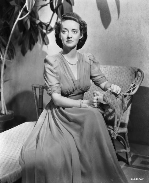<p>Bette Davis, wearing a long chiffon dress, sits on a basket table for her role as Leslie Crosbie in William Wyler's film noir <em>The Letter</em>.</p>