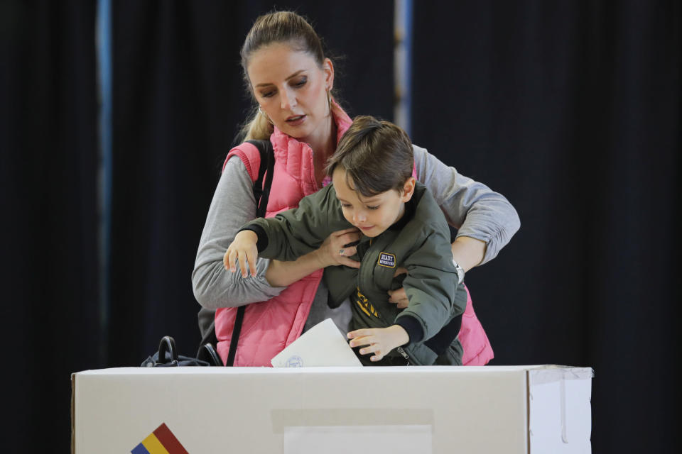 A woman holds a child to cast her vote in Bucharest, Romania, Sunday, Nov. 10, 2019. Voting got underway in Romania's presidential election after a lackluster campaign overshadowed by a political crisis which saw a minority government installed just a few days ago. (AP Photo/Vadim Ghirda)