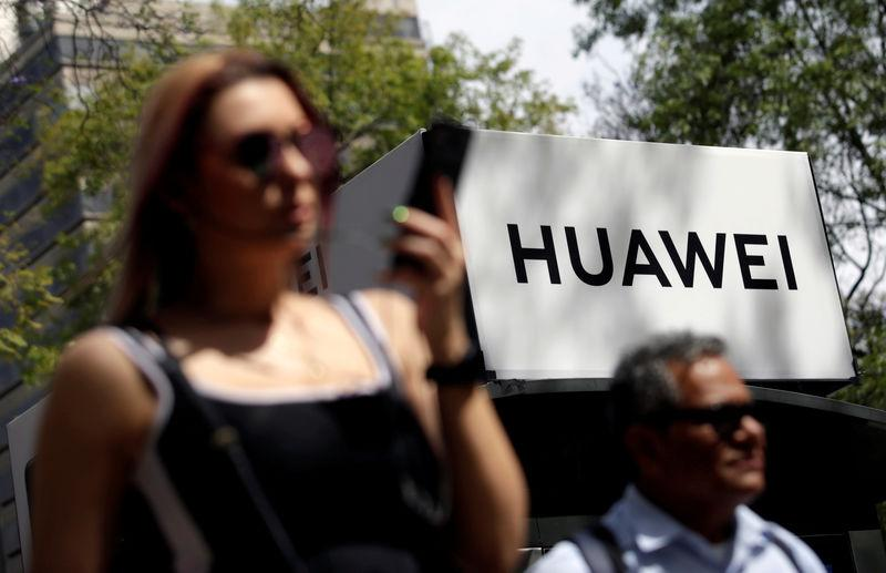 FILE PHOTO: People walk past a Huawei company logo at a bus stop in Mexico City, February 22, 2019. REUTERS/Daniel Becerril/File Photo