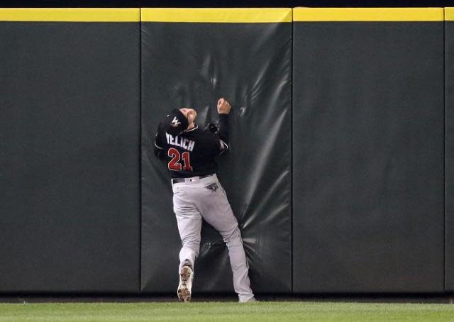 Miami Marlins center fielder Christian Yelich hits the outfield wall after robbing Seattle's Jarrod Dyson. (AP)