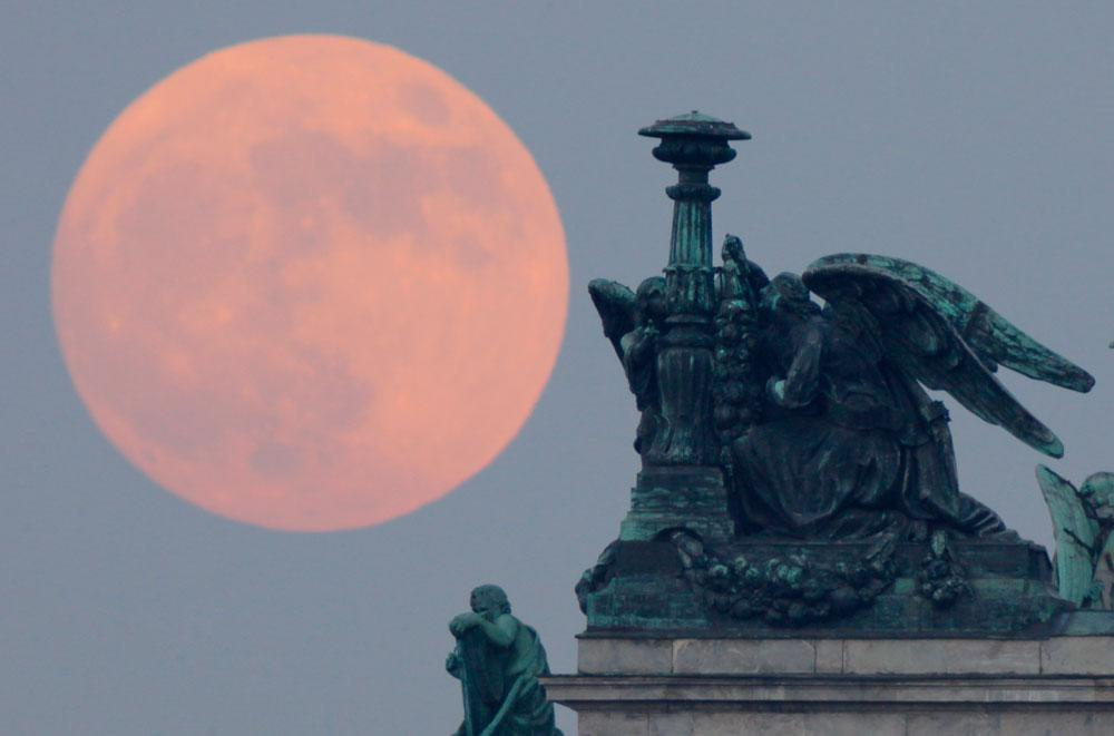 """The """"supermoon"""" rises behind statues of angels fixed at the St. Isaak's Cathedral in St.Petersburg, Russia, Saturday, May 5, 2012. Saturday's event is a """"supermoon,"""" the closest and therefore the biggest and brightest full moon of the year."""