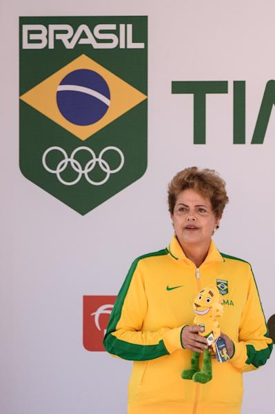 Brazilian President Dilma Rousseff, holding here the national Olympic team's mascot, is battling calls for her impeachment and claims she is victim of a coup (AFP Photo/Yasuyoshi Chiba)