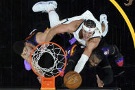 Denver Nuggets forward Aaron Gordon shoots over Phoenix Suns guard Devin Booker, left, and Phoenix Suns forward Jae Crowder, right, during the second half of Game 1 of an NBA basketball second-round playoff series, Monday, June 7, 2021, in Phoenix. (AP Photo/Matt York)