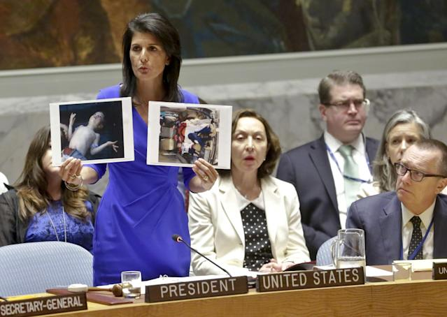 U.S. Ambassador to the U.N. Nikki Haley shows pictures of Syrian victims of chemical attacks as she addresses a meeting of the Security Council, April 5, 2017. (Photo: Bebeto Matthews/AP)