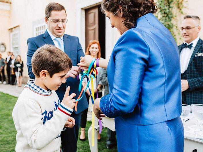 A boy stands between his parents as they tie ribbons around their wrists for their vow renewal.