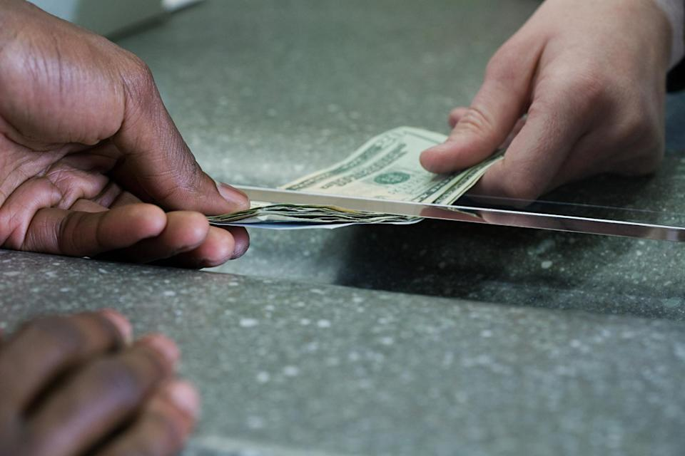 Cash being passed under a security window.