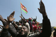 Supporters of Zambia's main opposition leader Hakainde Hichilema gather outside the party's offices, in Lusaka, Zambia, Saturday, Aug. 14, 2021. Early election results in Zambia show opposition leader Hakainde Hichilema ahead in a tight, tense race while the national Electoral Commission has urged people to wait for the final official results to avoid any unrest. (AP Photo/Tsvangirayi Mukwazhi)