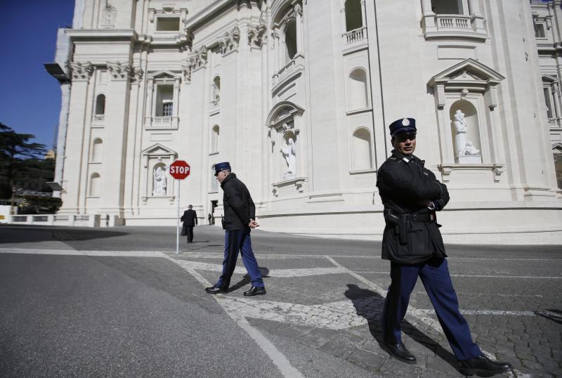 Vatican Police guards patrol in front of the St. Peter's Basilica, at the Vatican, Tuesday, Feb. 19, 2013. Last week, 85-year-old Pope Benedict XVI shocked the world by announcing his resignation. He will step down on Feb. 28, planning to retreat to a life of prayer in a monastery behind the Vatican's ancient walls. (AP Photo/Gregorio Borgia)