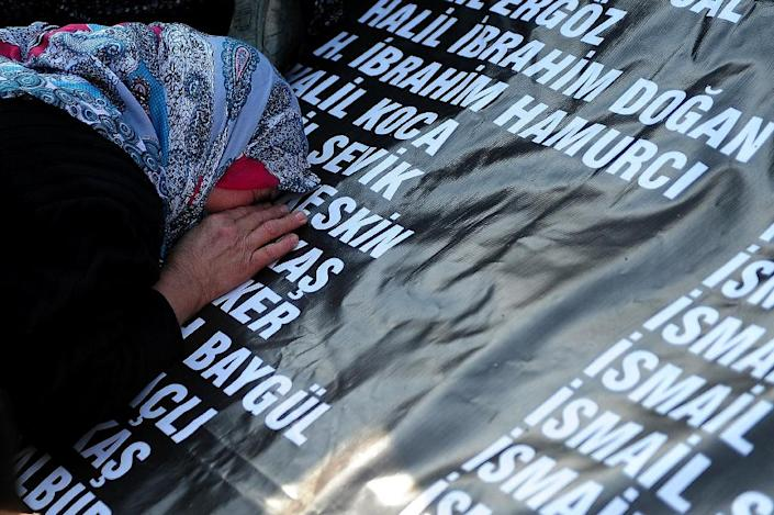 The mother of a dead miner cries in front of a list -- bearing the names of the 301 people killed in the 2014 disaster -- outside a special tribunal set up in Akhisar, western Turkey, on April 13, 2015 (AFP Photo/Ozan Kose)