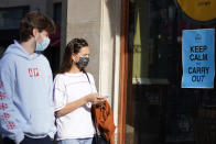 Pedestrians wear face masks as they pass a restaurant in downtown Evanston, Ill., Friday, Nov. 6, 2020. (AP Photo/Nam Y. Huh)