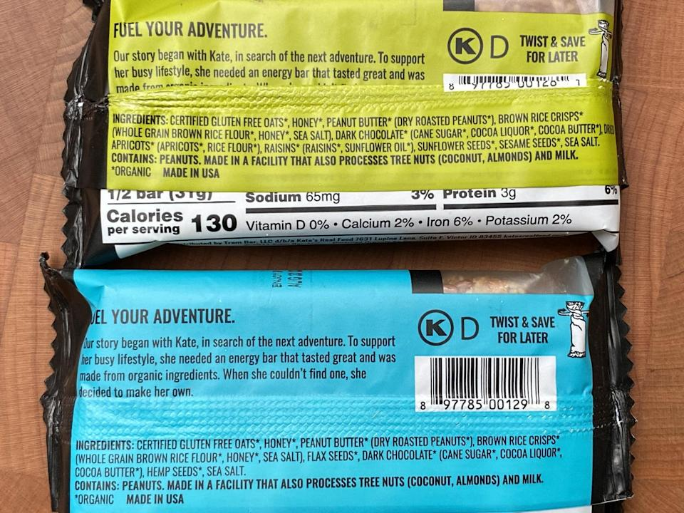 """<p>This photo shows the <a href=""""https://katesrealfood.com/shop/peanut-butter-dark-chocolate-12-pack"""" class=""""link rapid-noclick-resp"""" rel=""""nofollow noopener"""" target=""""_blank"""" data-ylk=""""slk:Peanut Butter Dark Chocolate"""">Peanut Butter Dark Chocolate</a> bar on the top and <a href=""""https://katesrealfood.com/shop/peanut-butter-hemp-flax-12-pack"""" class=""""link rapid-noclick-resp"""" rel=""""nofollow noopener"""" target=""""_blank"""" data-ylk=""""slk:Peanut Butter Hemp &amp; Flax"""">Peanut Butter Hemp &amp; Flax</a> bar on the bottom, just to give you an idea of the types of healthy ingredients you'll find in Kate's Real Food bars. </p> <p>While all eight bars are gluten-free, they're not vegan, since they contain honey. Seven of the eight flavors are also dairy-free except for the Peanut Butter Milk Chocolate flavor. </p>"""