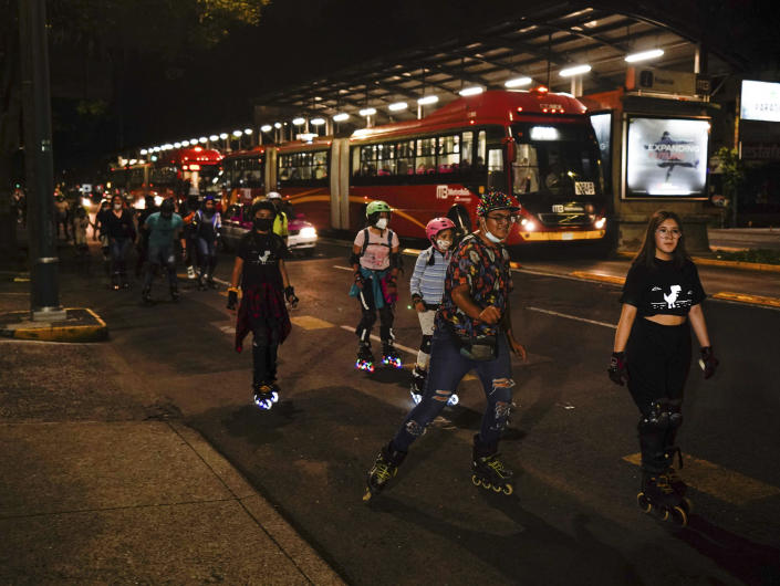 Youths rollerblade along Insurgentes Avenue in Mexico City, Friday, July 23, 2021. Hours after Mexico City authorities raised the alert level in the face of rising COVID-19 infections, many residents of the capital's trendy Coyoacan neighborhood crammed its center ignoring social distancing and forgoing masks. (AP Photo/Fernando Llano)