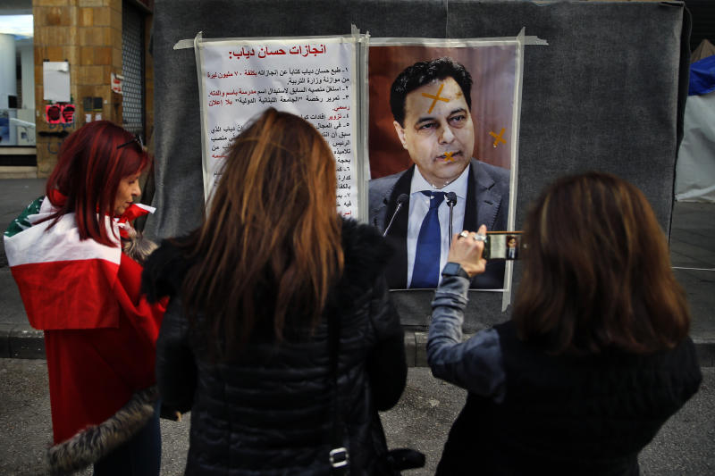 Protesters take pictures with their mobile phones of a defaced poster of newly-nominated Lebanese Prime Minister, Hassan Diab, and a list of what the protesters call the premier's achievements when he was minister of higher education, in downtown Beirut, Lebanon, Sunday, Dec. 22, 2019. (AP Photo/Bilal Hussein)