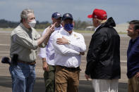 President Donald Trump talks with Sen. John Kennedy, R-La., left, and Louisiana Gov. John Bel Edwards upon arrival at Chennault International Airport, Saturday, Aug. 29, 2020, in Lake Charles, La. Trump is planning to tour damage from Hurricane Laura in Texas and Louisiana. Rep. Mike Johnson, R-La., is at far right. (AP Photo/Alex Brandon)