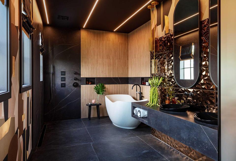 "<p>In her ""Modern Afro-Inspired Palm Beach Retreat,"" White brought the drama with dark hues—like slabs of grained Cosentino on the floor, shower, and custom vanity—and metallic accents, including gold pendant lights and a backsplash in a bronze, 3D tile that serves as a work of art in and of itself. <strong>To get the look of a warm wood—without warping from bathroom moisture—White turned to a tile that looks like bamboo but is much more durable. </strong></p>"