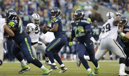 Seattle Seahawks quarterback Tarvaris Jackson, third from left, looks to pass against the Oakland Raiders in the first half of an NFL preseason football game on Thursday, Aug. 29, 2013, in Seattle. (AP Photo/Stephen Brashear)
