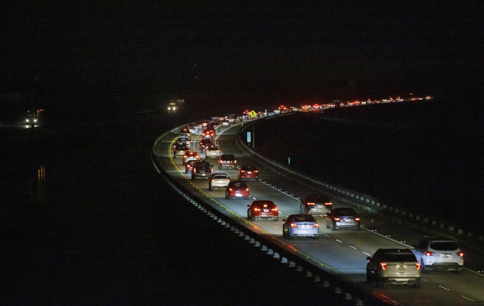 """Westbound I-10 traffic on the Bonnet Carré Spillway is slow going at 4:00 a.m. near Kenner, La. Saturday, Aug. 28, 2021, as many New Orleans area residents evacuate ahead of Hurricane Ida. Residents across Louisiana's coast are taking one last day to prepare for what is being described as a """"life-altering"""" Hurricane Ida. The storm is expected to bring winds as high as 140 mph (225 kph) when it slams ashore. (David Grunfeld, NOLA.com/The Times-Picayune/The New Orleans Advocate via AP)"""