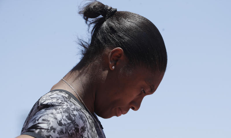 South Africa's Caster Semenya looks down against a blue sky.