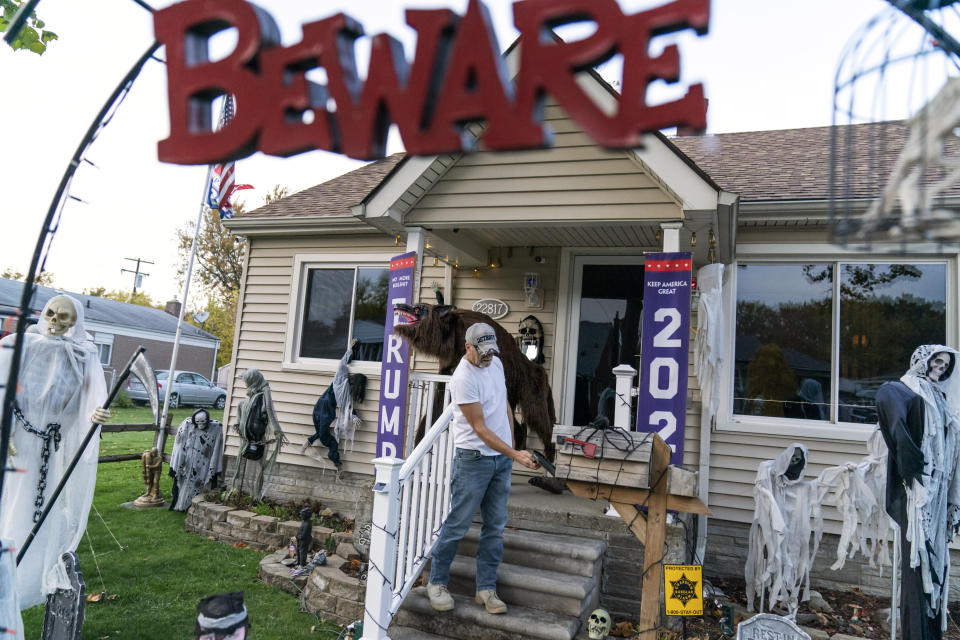 """Trump supporter Terry Frandle checks his mailbox in his front yard decorated for Halloween and a Trump reelection campaign in Saint Clair Shores, Mich., Wednesday, Oct. 28, 2020. In Macomb County, Frandle hung Trump banners outside his house and noticed that neighbors who used to stop to chat crossed to the other side of the street, not even offering a """"hello."""" Some drivers wave, some flip the bird. He doesn't blame Trump for the discord, he blames Democrats and the media for failing to give Trump a fair shake, he said. He plans to vote in person on Election Day. """"I just don't trust anything anymore,"""" he said, except for what he hears directly from Trump. (AP Photo/David Goldman)"""