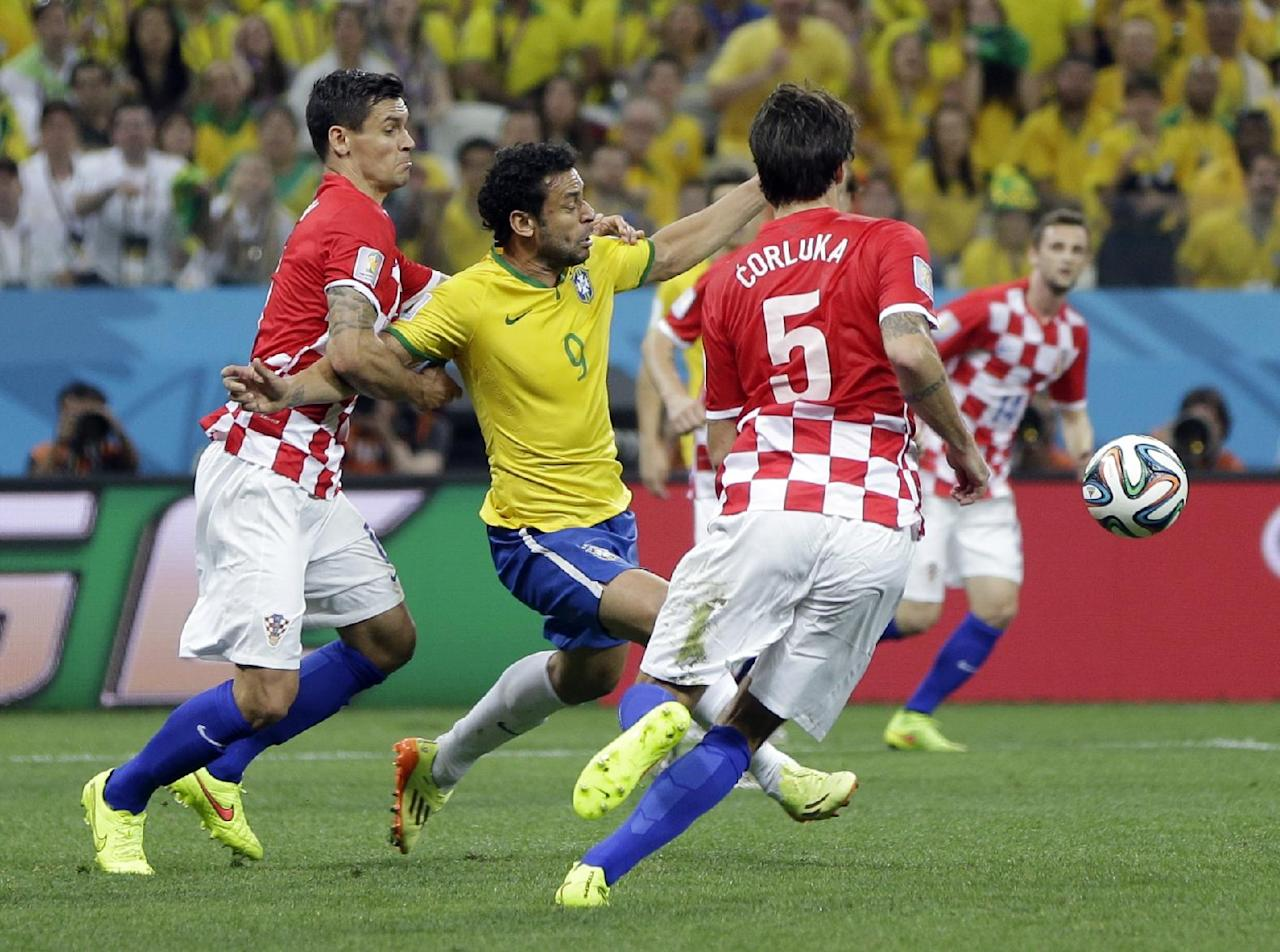 Brazil's Fred (9) is taken down by Croatia's Dejan Lovren, left, during the group A World Cup soccer match between Brazil and Croatia, the opening game of the tournament, in the Itaquerao Stadium in Sao Paulo, Brazil, Thursday, June 12, 2014.  (AP Photo/Andre Penner)