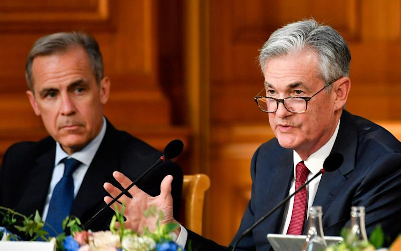 Jerome Powell, right, said central banks must be as transparent as possible to keep their legitimacy in the eyes of the public. Mark Carney, left, said introducing a new digital currency is not on the Bank of England's agenda for now - Bloomberg