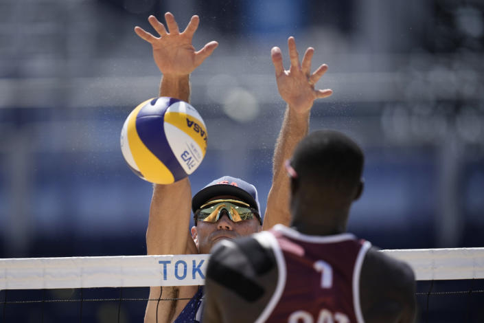 Philip Dalhausser, left, of the United States, trees to block the shot of Cherif Younousse, of Qatar, during a men's beach volleyball match at the 2020 Summer Olympics, Sunday, Aug. 1, 2021, in Tokyo, Japan. (AP Photo/Felipe Dana)