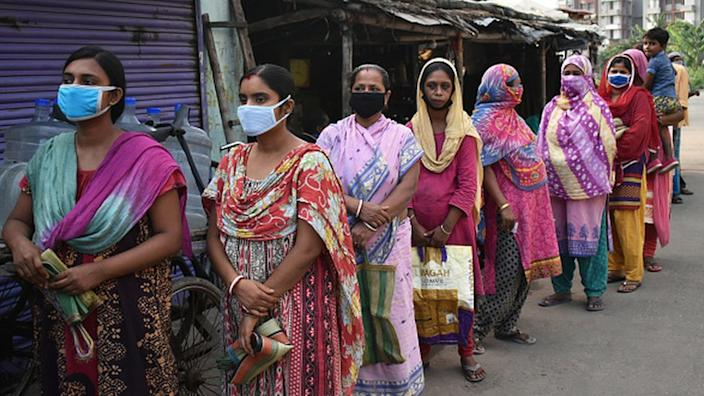 Women stand in a queue to get free ration in Kolkata
