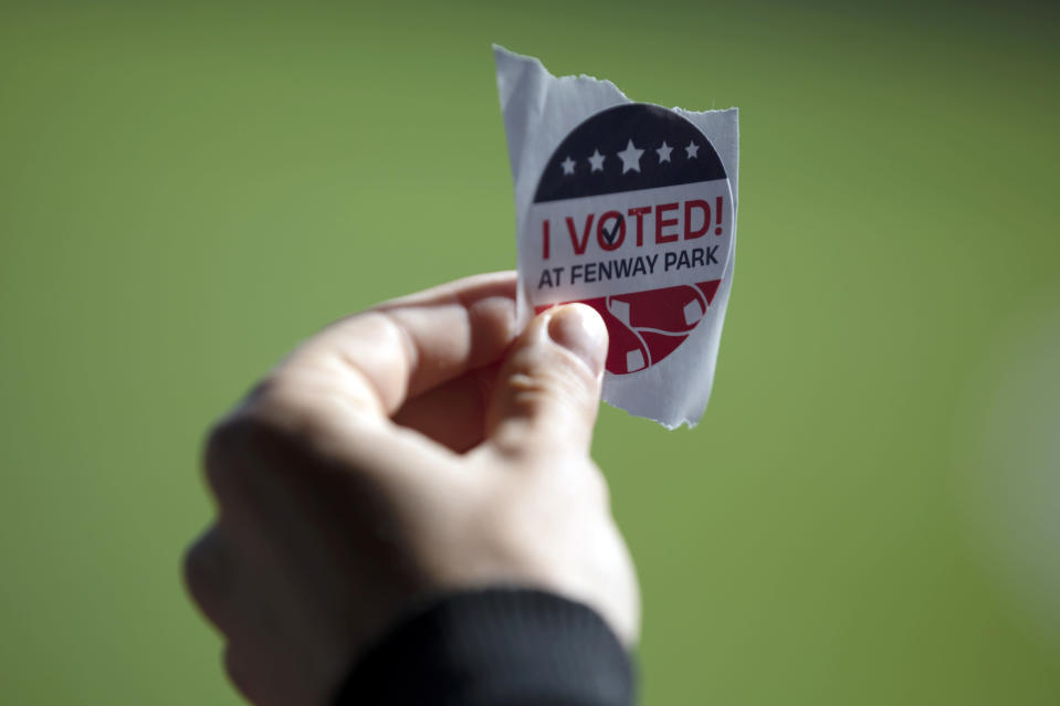 A voter holds a sticker after casting a ballot at Fenway Park, Saturday, Oct. 17, 2020, in Boston. (AP Photo/Michael Dwyer)