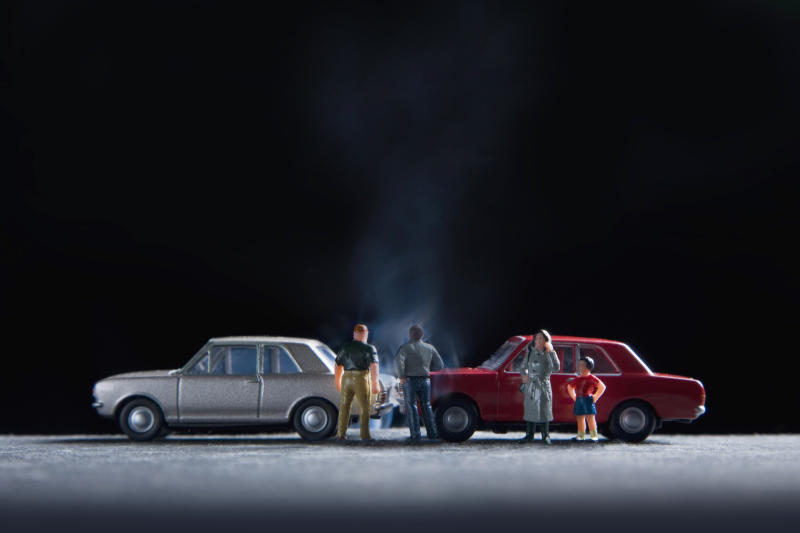model people gathered around a model car crash
