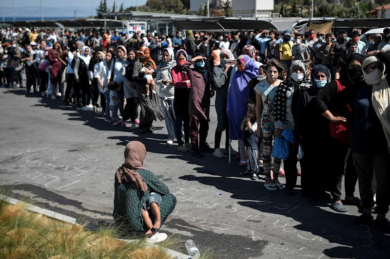 Migrants who became homeless after a major fire burned Greeece's largest Moria refugee camp queue during a water and food distribution at a supermarket's parking where many of them camp on September 10, 2020. - Thousands of asylum seekers on the Greek island of Lesbos languished on roadsides on Thursday, homeless and hungry after the country's largest camp burned down, with local officials stonewalling government efforts to create new temporary shelters. (Photo by LOUISA GOULIAMAKI / AFP)