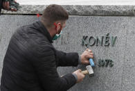 A worker removes sign from the pedestal of the statue of a Soviet World War II commander Marshall Ivan Stepanovic Konev after its been removed from its site in Prague, Czech Republic, Friday, April 3, 2020. Marshall Konev led the Red Army forces that liberated Prague and large parts of Czechoslovakia from the Nazi occupation in 1945. His monument, unveiled in the Prague 6 district in 1980 when the country was occupied by Soviet troops, has been a source of controversy. (AP Photo/Petr David Josek)
