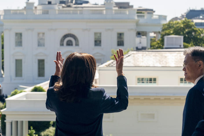 The White House and West Wing are visible as Vice President Kamala Harris, left, meets with South Korean President Moon Jae-in, right, on a balcony of the Eisenhower Executive Office Building in the White House complex in Washington, Friday, May 21, 2021. (AP Photo/Andrew Harnik)