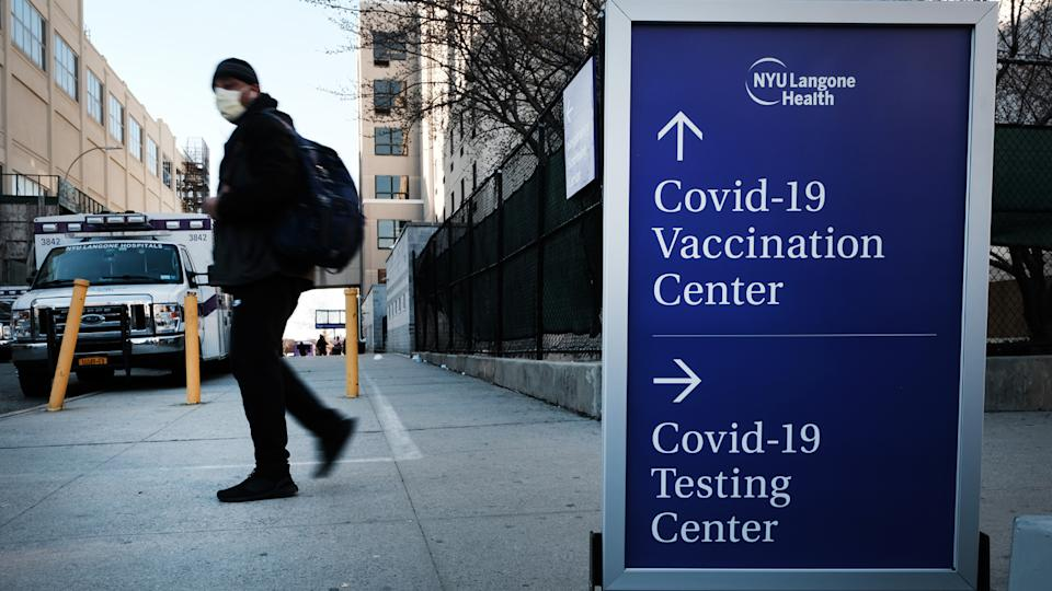 People walk by a sign for both a Covid-19 testing clinic and a Covid vaccination location outside of a Brooklyn hospital on March, 29 2021 in the Brooklyn borough of New York City. (Spencer Platt/Getty Images)