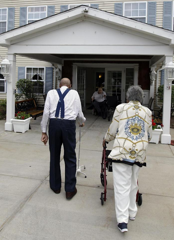 Roland Davis and Lena Henderson, both 85, walk back to an apartment complex after posing for photos in West Seneca, N.Y., Tuesday, July 31, 2012. They got married while still in their teens, divorced 20 years later and are getting remarried after nearly a half-century apart. (AP Photo/David Duprey)