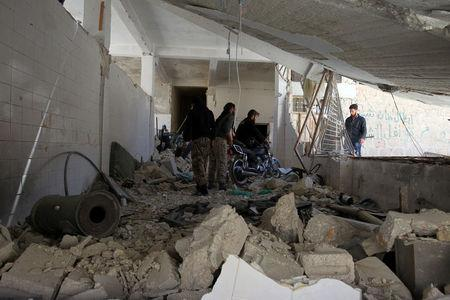 Men salvage a motorbike amid the damage inside a medical point at a site hit by airstrikes on Tuesday, in the town of Khan Sheikhoun in rebel-held Idlib, Syria April 5, 2017. REUTERS/Ammar Abdullah