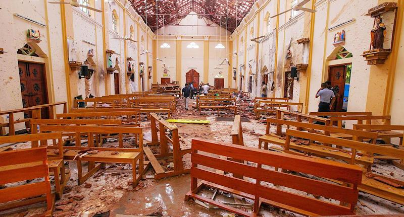 Crime scene officials inspect the site of a bomb blast inside St Sebastian's Church. Source: Reuters