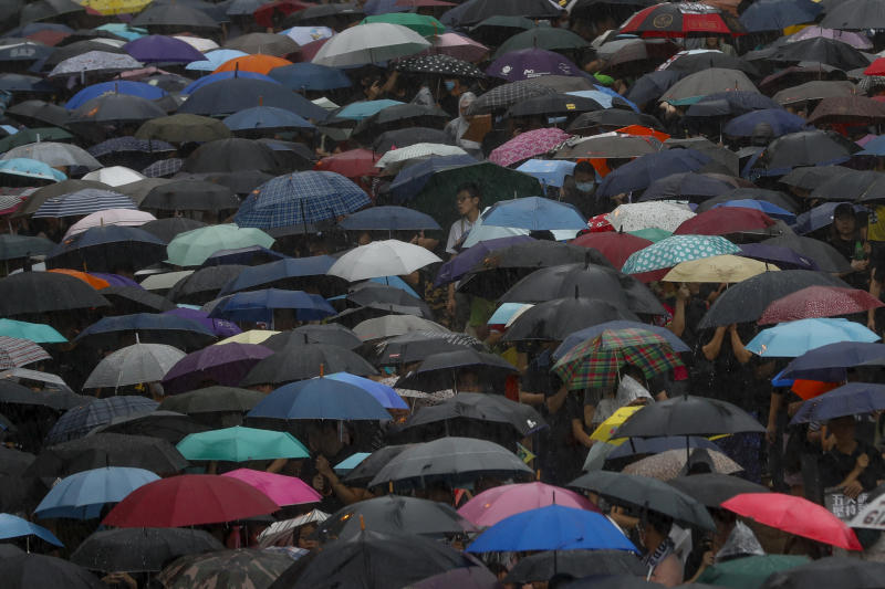 Protesters with umbrellas brave the rain during a rally in Hong Kong Sunday, Aug. 18, 2019. People are streaming into a park in central Hong Kong for what organizers hope will be a peaceful demonstration for democracy in the semi-autonomous Chinese territory. (AP Photo/Vincent Thian)