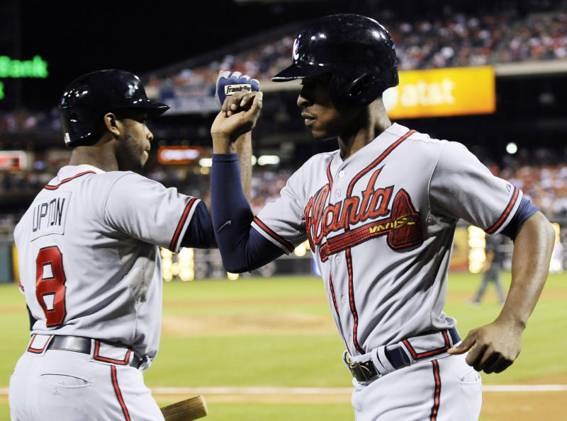 Atlanta Braves' B.J. Upton, right, celebrates with Justin Upton after scoring on a Jason Heyward single to deep right in the fourth inning of a baseball game on Sunday, Aug. 4, 2013, in Philadelphia. (AP Photo/Michael Perez)