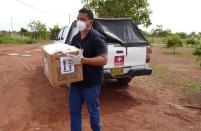 A man wearing a face mask carries a box with a test for the coronavirus disease (COVID-19), in Cumaribo