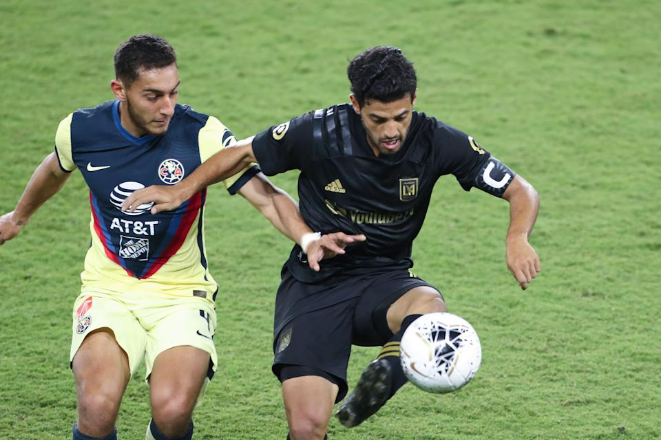 ORLANDO, FL - DECEMBER 19: Sebastian Caceres #4 of Club America and Carlos Vela #10 of Los Angeles FC fight for the ball during the CONCACAF Champions League semifinal game at Exploria Stadium on December 19, 2020 in Orlando, Florida. (Photo by Alex Menendez/Getty Images)