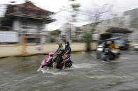 Residents wear masks to prevent the spread of the coronavirus ride motorcycles as they negotiate a flooded road due to Typhoon Molave in Pampanga province, northern Philippines on Monday, Oct. 26, 2020. A fast moving typhoon has forced thousands of villagers to flee to safety in provinces. (AP Photo/Aaron Favila)
