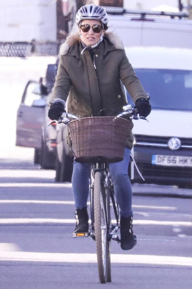 <p>Pippa Matthews rides her bike through West London on Monday wearing a green fur-lined parka and black suede boots.</p>