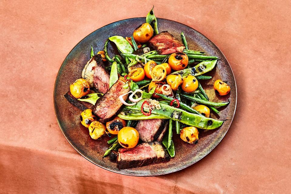 """Grill cherry tomatoes in a skillet alongside strip steaks until charred and saucy, then toss them with fresh tomatoes, garlic, and red chile for a sweet, tangy, perfect summer sauce. <a href=""""https://www.epicurious.com/recipes/food/views/grilled-strip-steak-with-blistered-tomatoes-and-green-beans?mbid=synd_yahoo_rss"""" rel=""""nofollow noopener"""" target=""""_blank"""" data-ylk=""""slk:See recipe."""" class=""""link rapid-noclick-resp"""">See recipe.</a>"""
