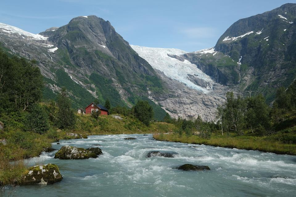 The Boyabreen glacier in Norway lies above rock it ground smooth and once covered deep in ice. Meltwater rushes down a stream past cabins in August 2020. (Photo: Sean Gallup via Getty Images)