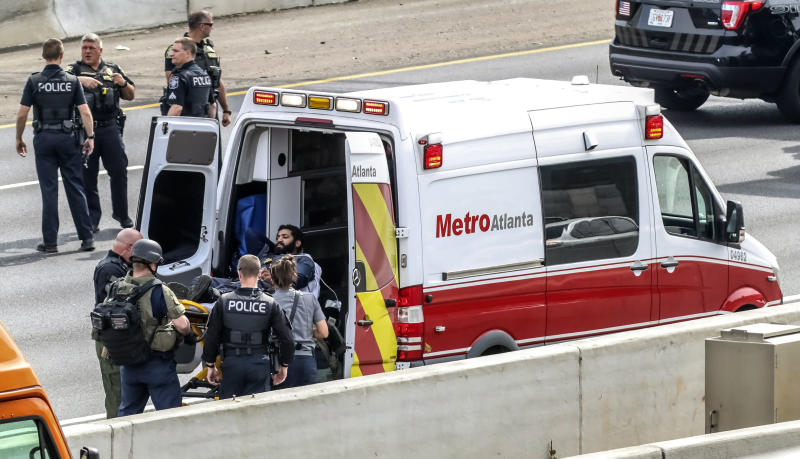Police officers place a man they detained into an ambulance following a standoff along the southbound lanes of Interstate 75, Friday, March 29, 2019, near Marietta, Ga., northwest of Atlanta. Marietta police said an armed driver had stopped on the freeway and wasn't cooperating with officers. Police had followed the vehicle to I-75 since it matched the description from an armed robbery nearby. (John Spink/Atlanta Journal-Constitution via AP)