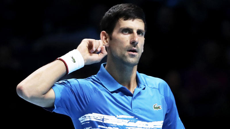 Novak Djokovic gesturing that he can't hear the crowd.