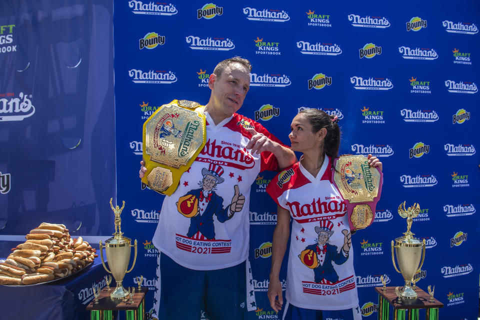 Winners Joey Chestnut and Michelle Lesco pose with their championship belts and trophies at the Nathan's Famous Fourth of July International Hot Dog-Eating Contest in Coney Island's Maimonides Park on Sunday, July 4, 2021, in Brooklyn, New York. (AP Photo/Brittainy Newman)
