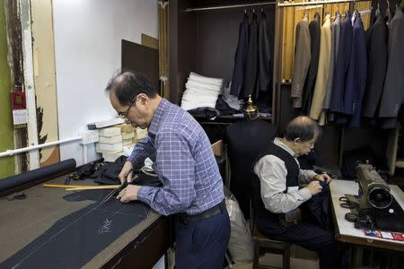 Tailors work at a workshop at Hong Kong's Tsim Sha Tsui shopping district January 22, 2015. REUTERS/Tyrone Siu