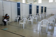 A woman sits in the nearly empty waiting room of a vaccination center in Lisbon, Tuesday, Sept. 21, 2021. As Portugal nears its goal of fully vaccinating 85% of the population against COVID-19 in nine months, other countries want to know how it was able to accomplish the feat. A lot of the credit is going to Rear Adm. Henrique Gouveia e Melo. (AP Photo/Armando Franca)